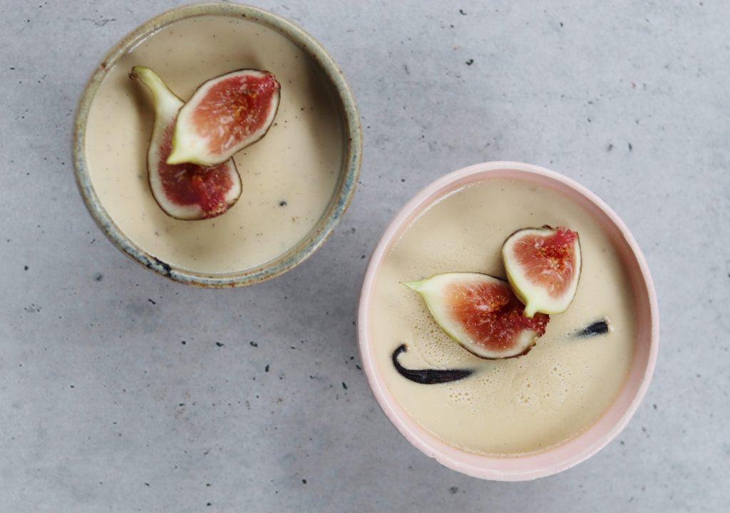 two ceramic bowls filled with coconut vanilla custard, vanilla bean and fresh figs
