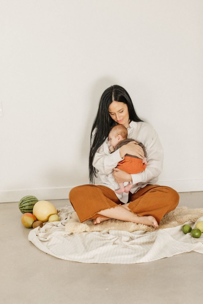 Mother holding her baby sitting on the floor surrounded by fruit